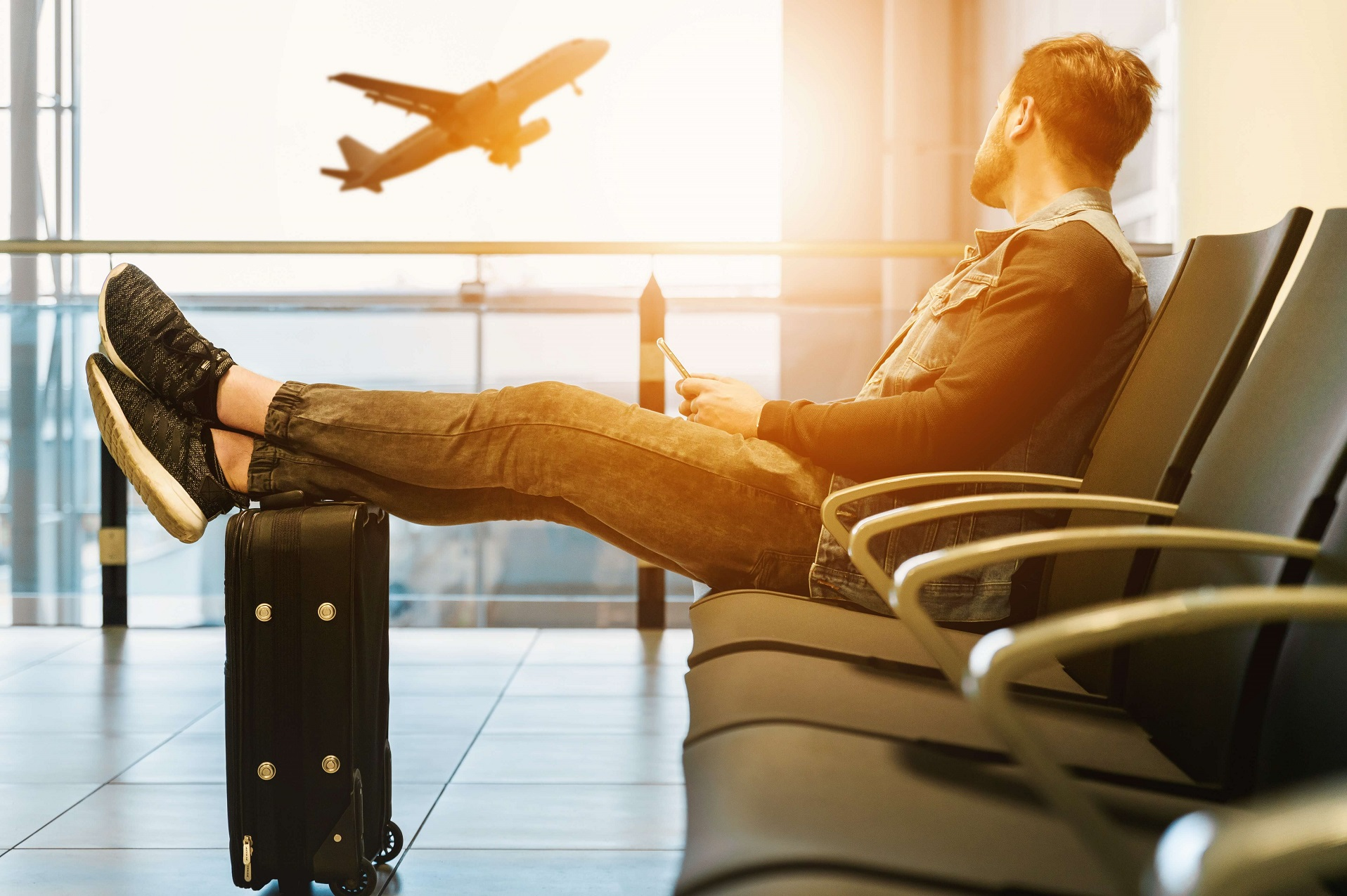 Man Sitting On Chair With Feet On Luggage